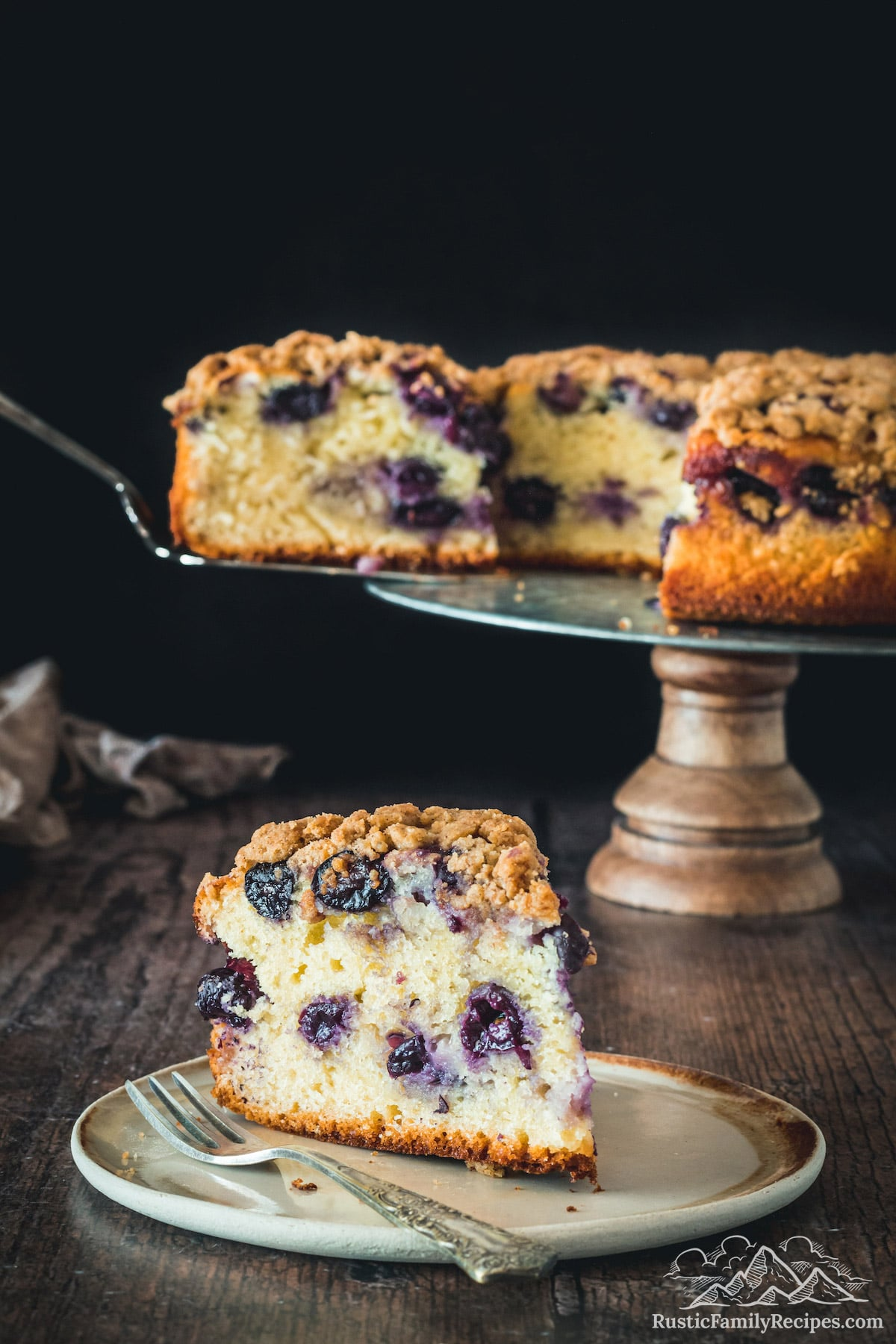 Slice of black currant cake in front of the entire cake on a stand