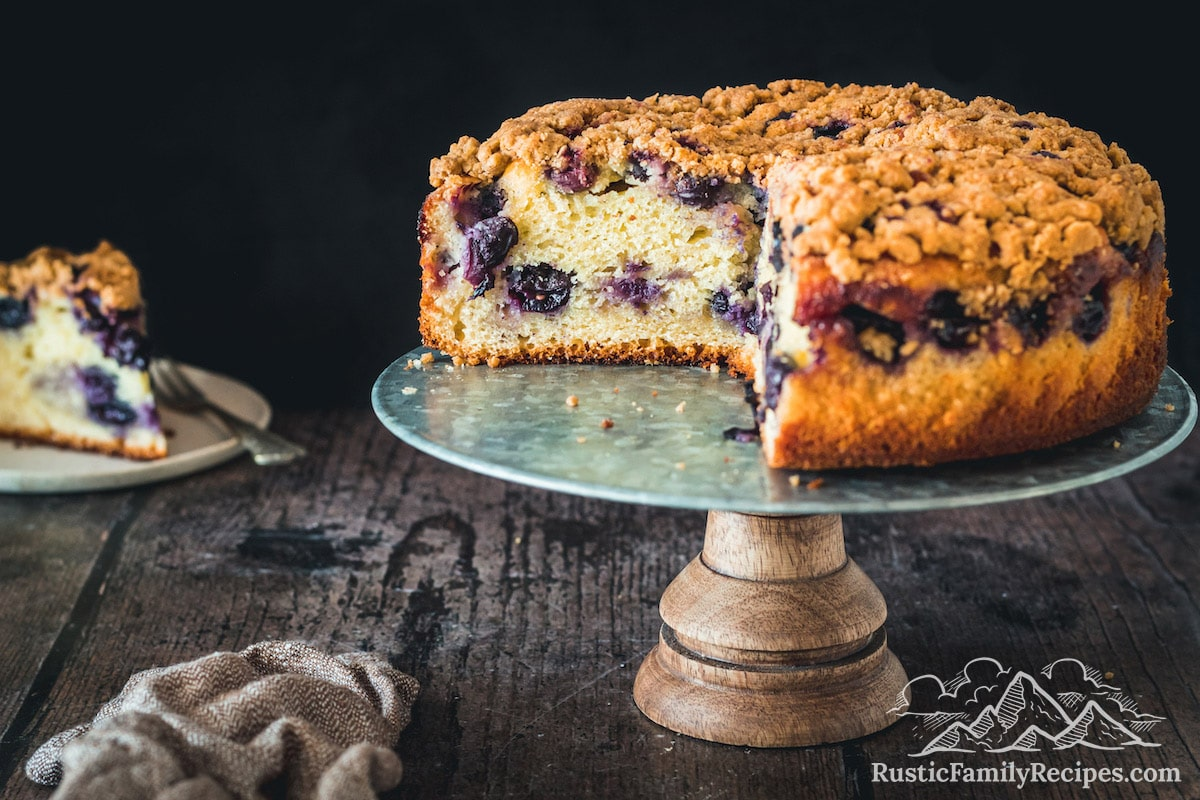 Black currant cake on a stand with slices taken out