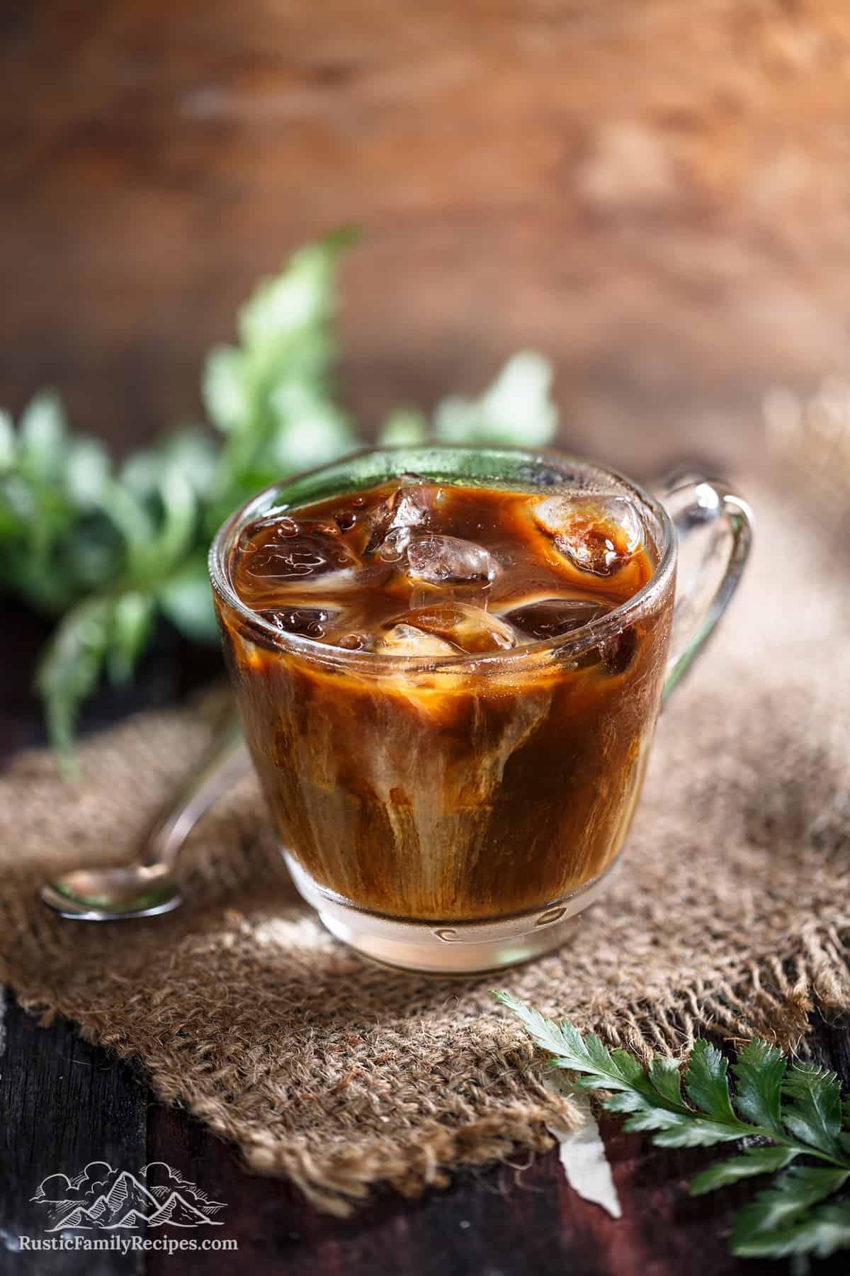 A glass mug with cardamom iced coffee