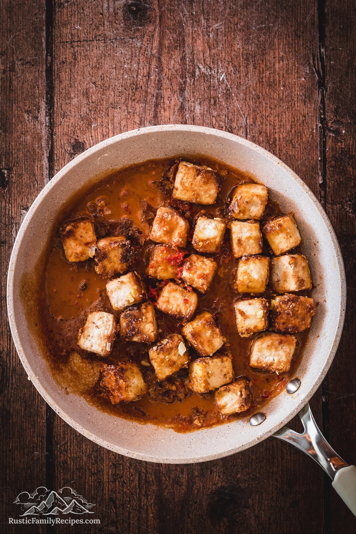 Tofu cubes cooking in skillet with orange sauce