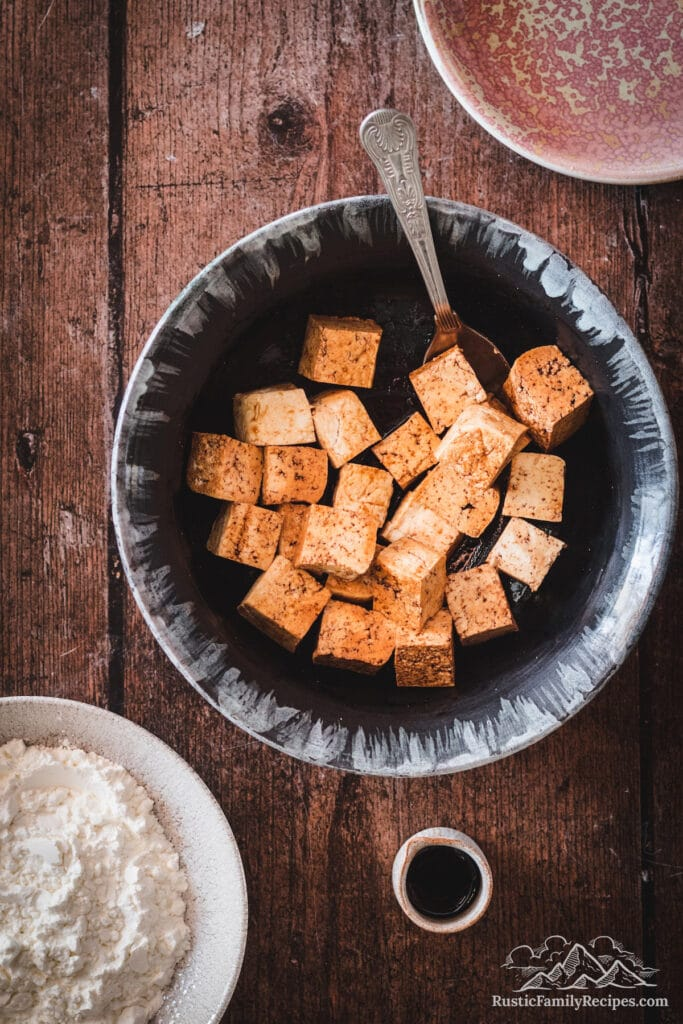 Overhead shot of tofu cubes being tossed with soy sauce