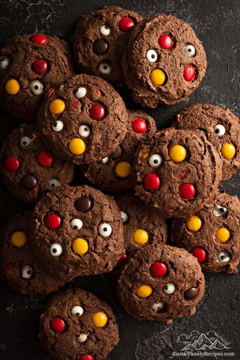 A pile of chocolate cookies with M&M candies and candy eyes.