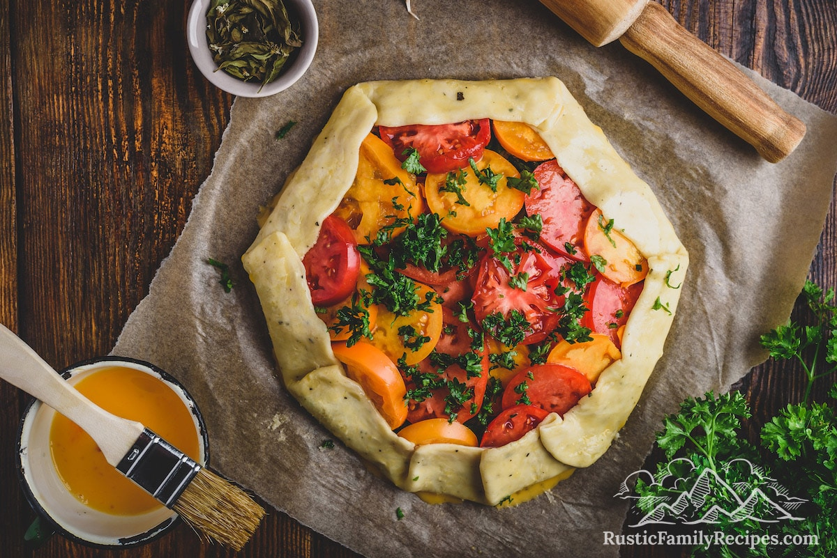 Unbaked tomato galette next to a rolling pin and pastry brush