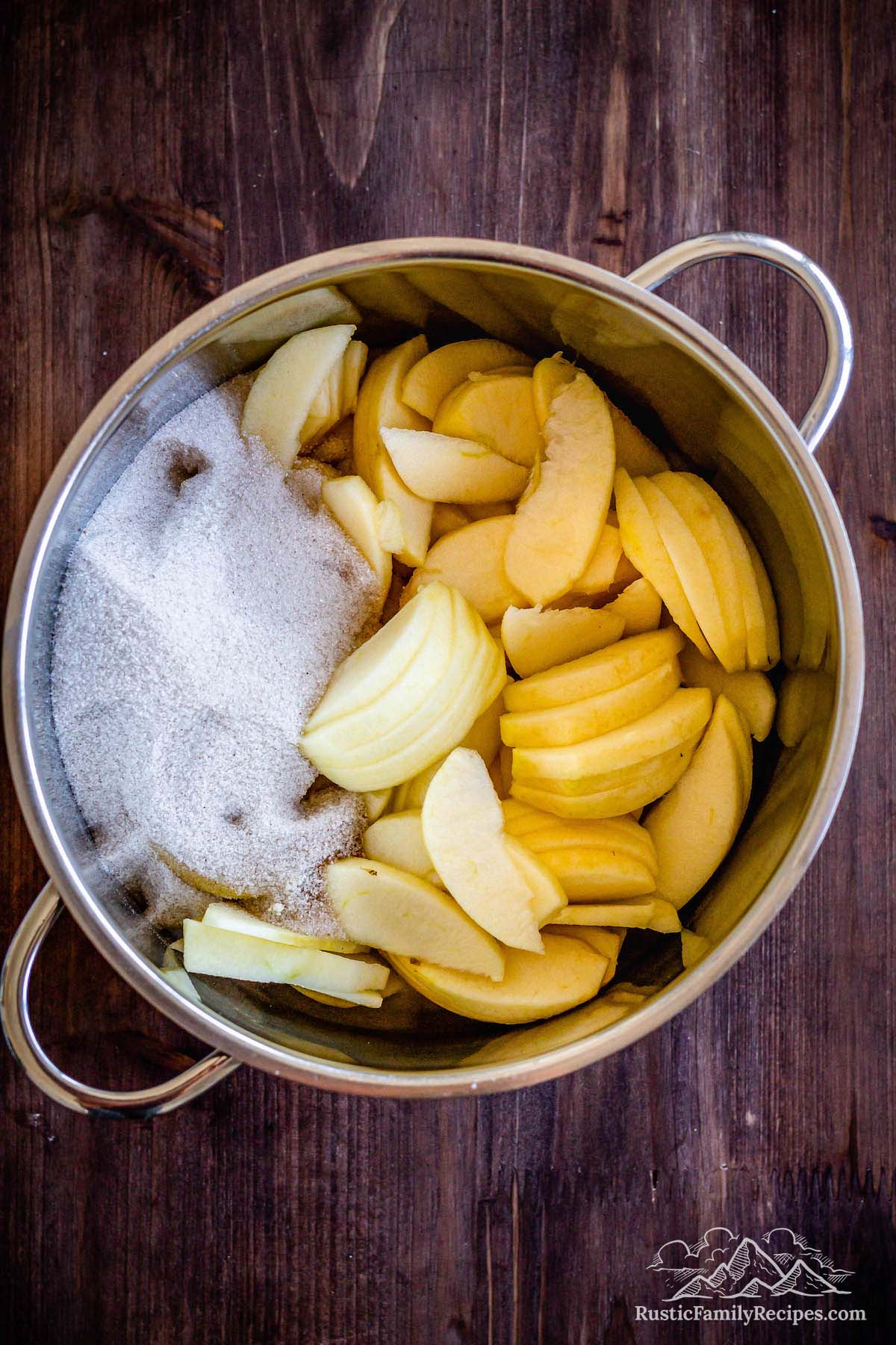 Sliced apples in a pot with cinnamon sugar