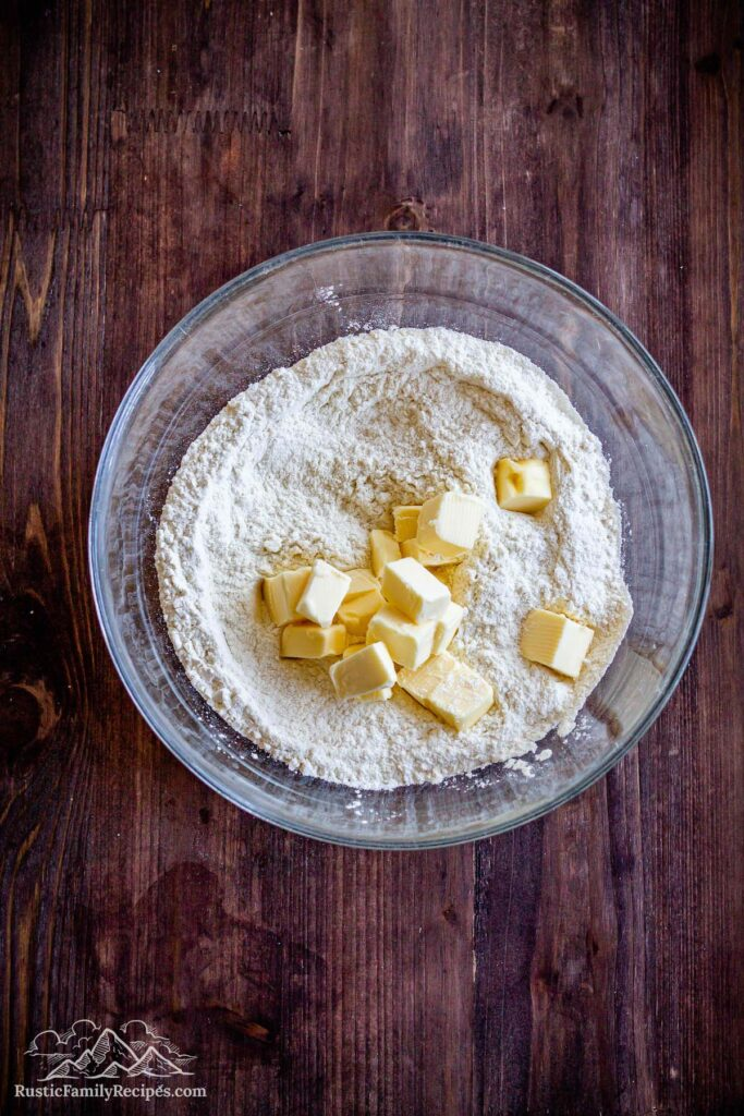 A glass bowl with flour and cubed butter