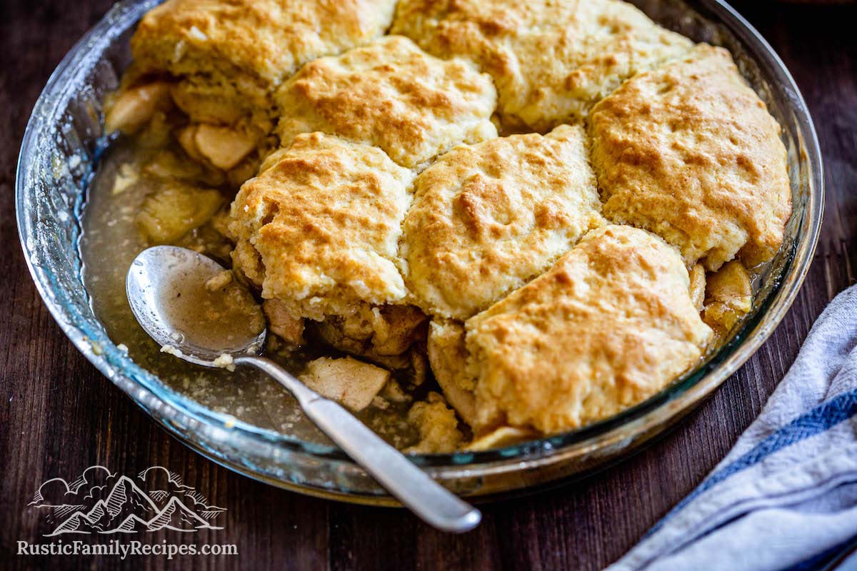 Apple cobbler in a pie pan with a spoon