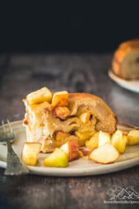 Slice of Apple Harvest Bread on plate with apples scattered around it