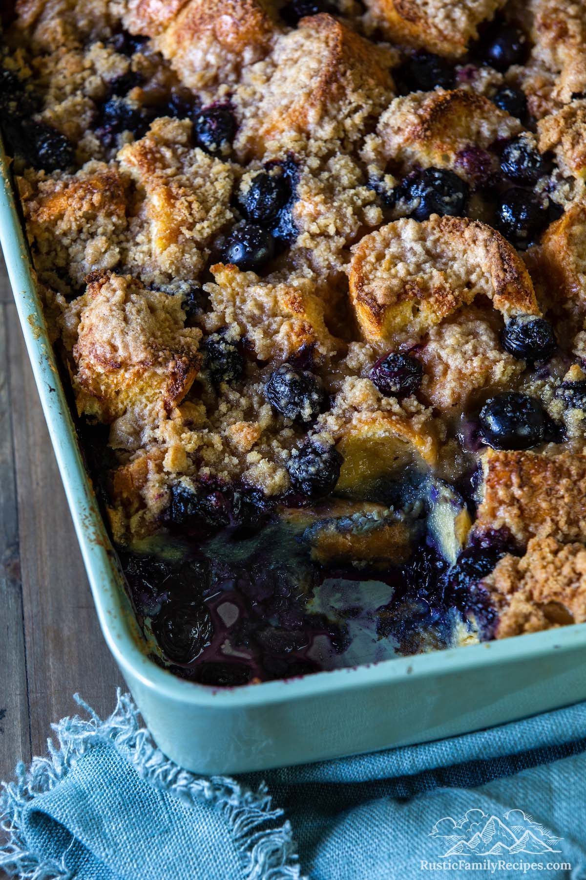 Blueberry french toast bake in a casserole dish with a slice taken out