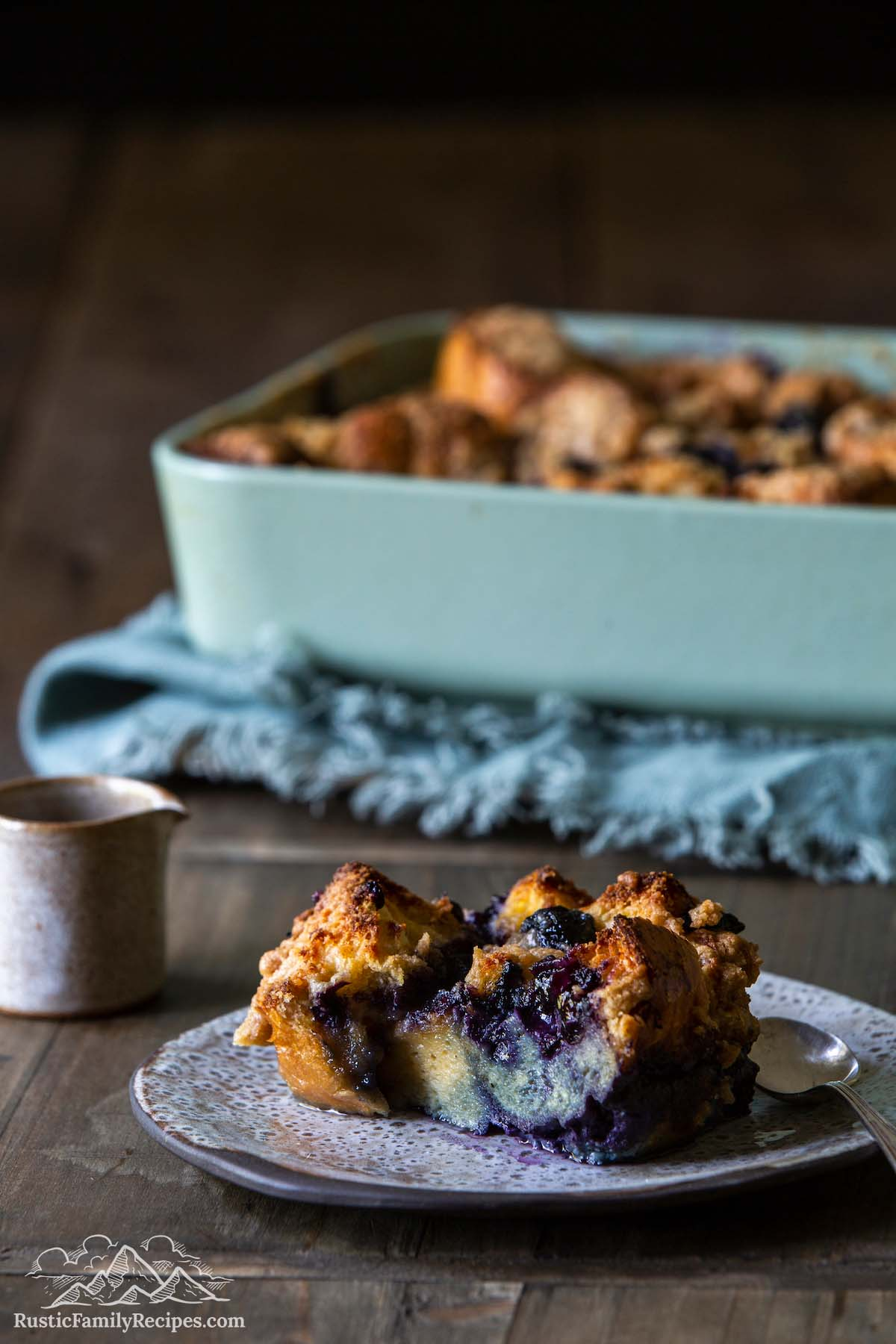 A slice of french toast casserole in front of a blue baking dish