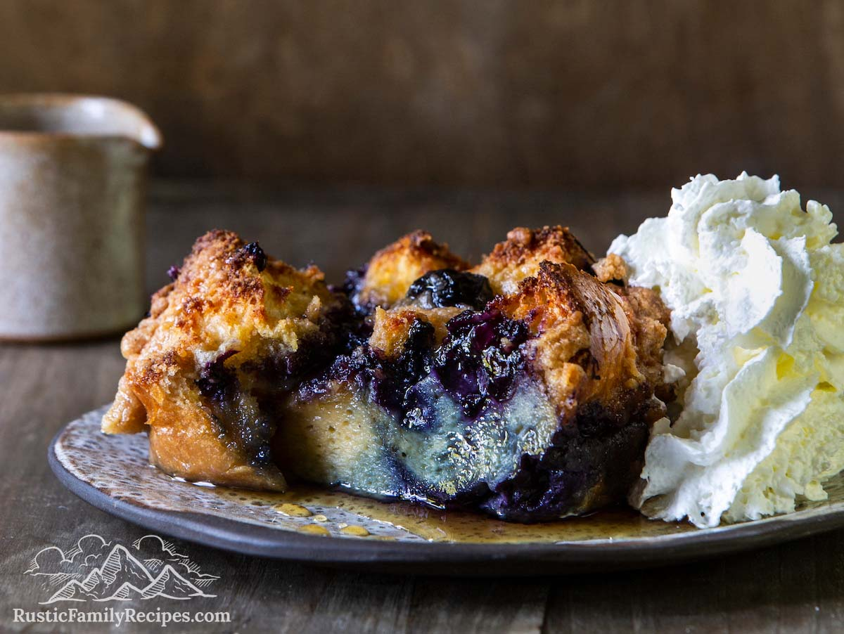 Slice of blueberry french toast bake with syrup and whipped cream