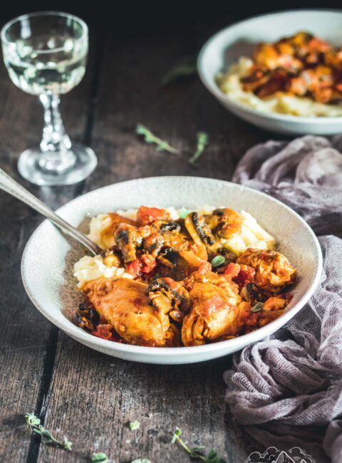Two rustic bowls with chicken chasseur and mashed potatoes