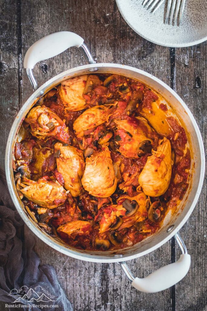 Chicken chasseur cooking in a dutch oven