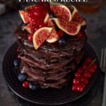 A tall stack of chocolate pancakes with figs, blueberries and currants