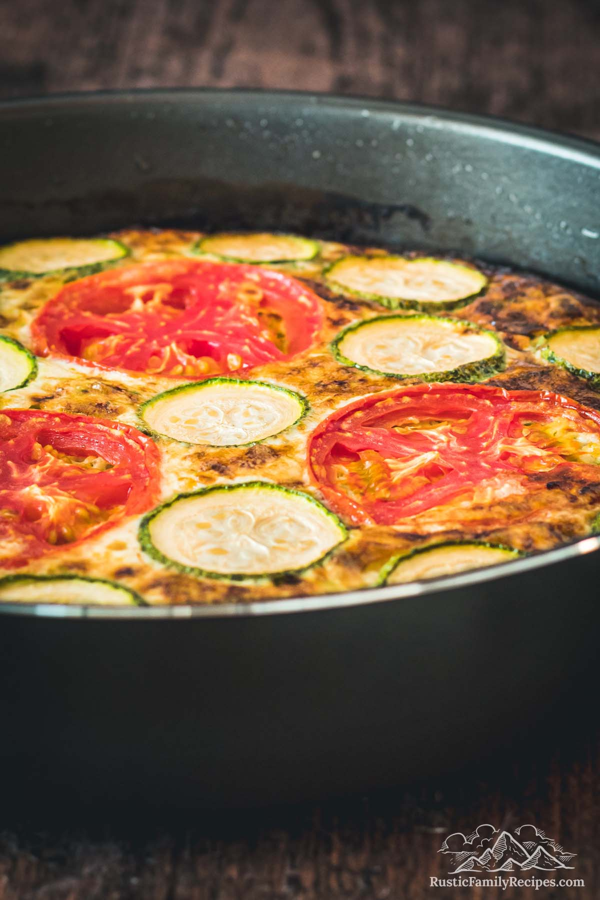 Side view of baked crustless zucchini quiche in a pan