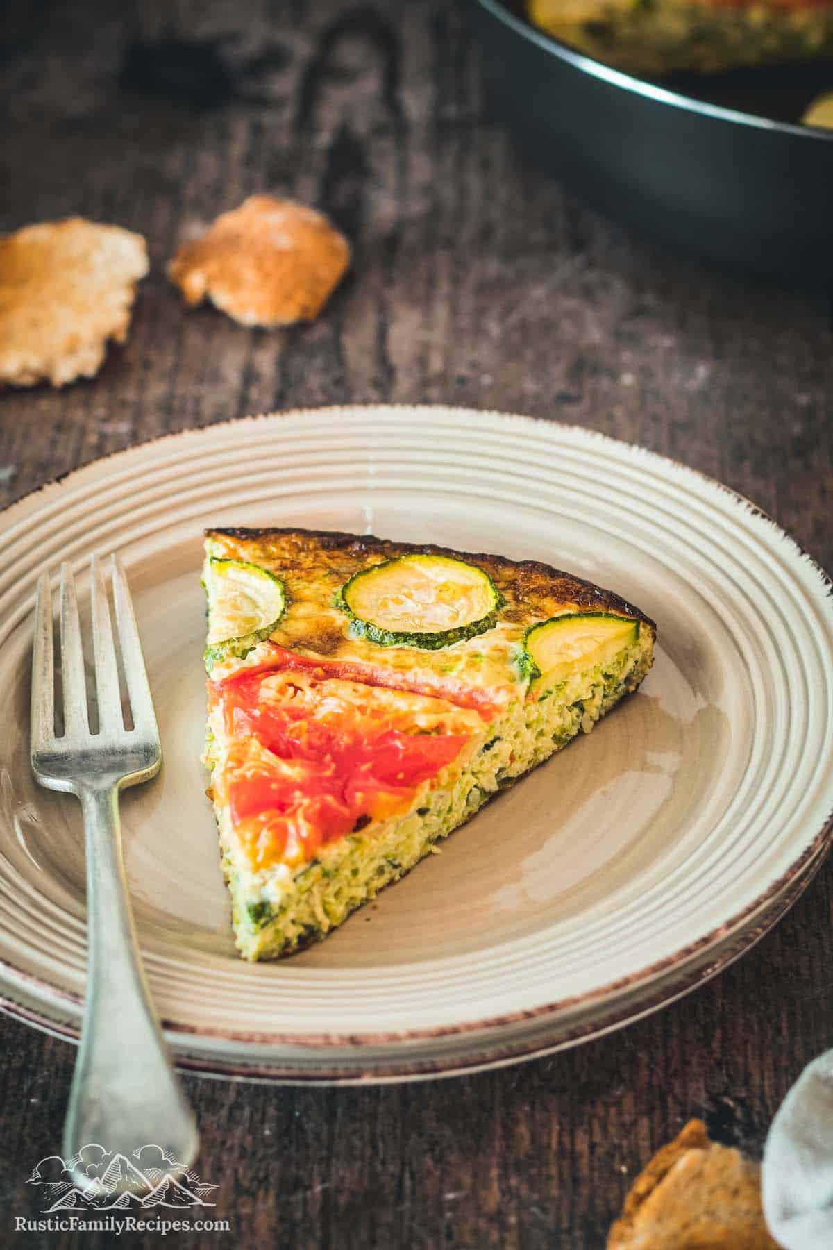 Slice of zucchini quiche on a white plate