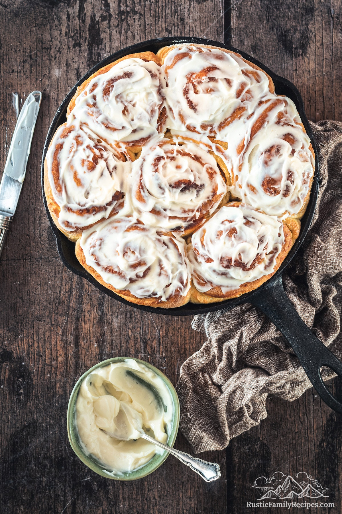 Overhead shot of Sourdough Cinnamon Rolls in skillet with bowl of frosting
