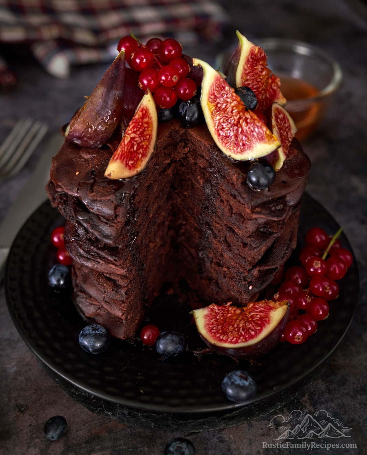 tall stack of chocolate pancakes topped with fruit with a cut taken out of the stack