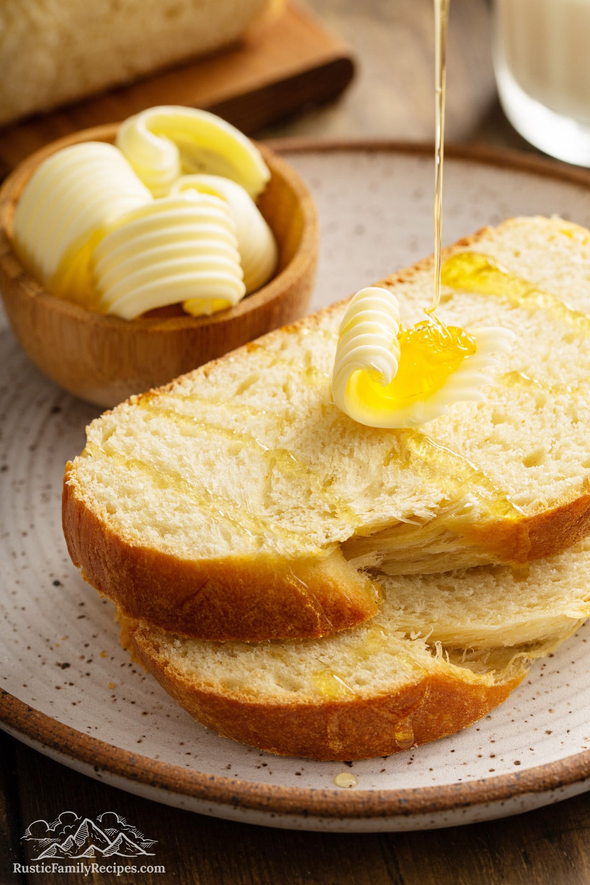 Two slices of Honey Vanilla Challah topped with butter and honey