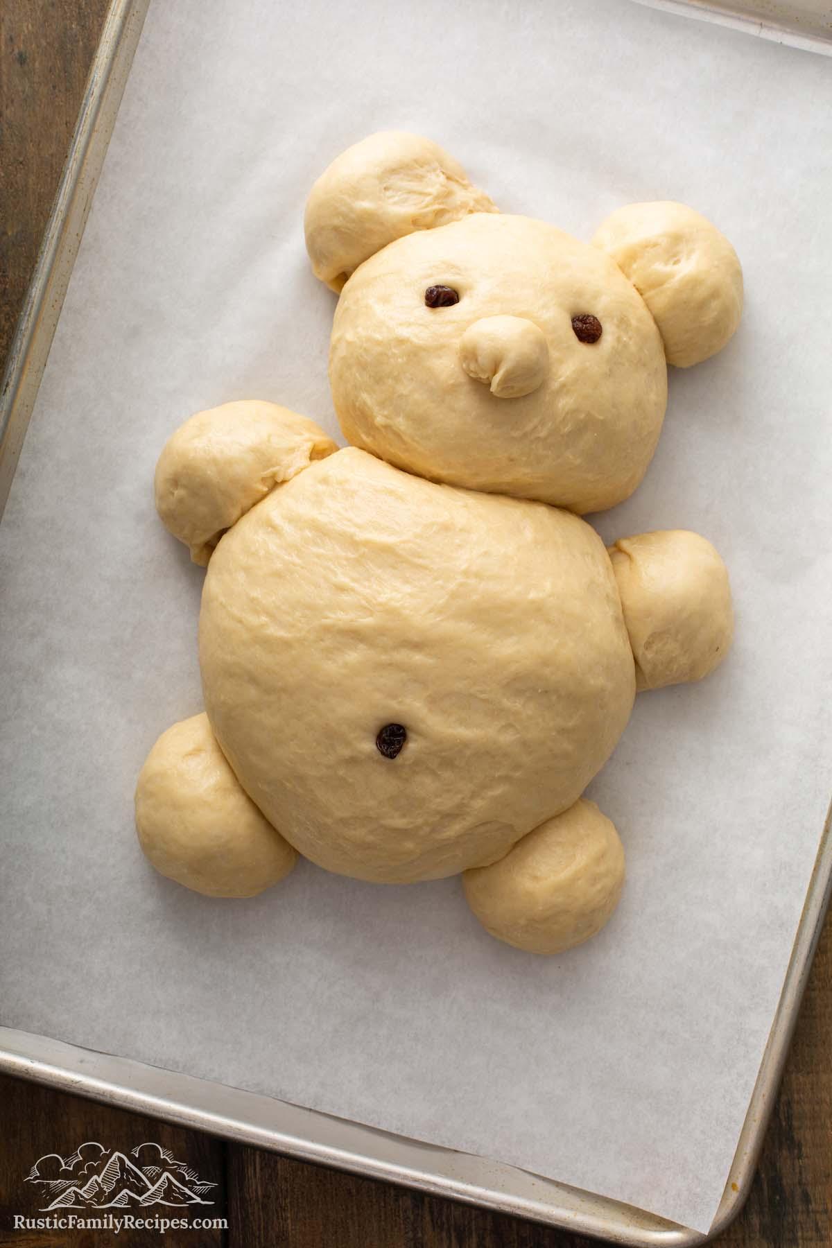 Unbaked challah dough shaped like a teddy bear