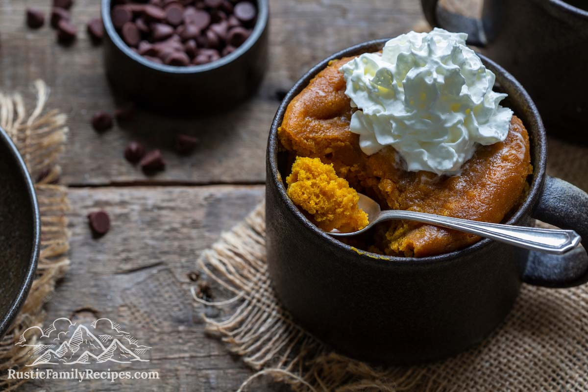 Pumpkin Mug Cake with whipped cream, spoon taking a scoop out