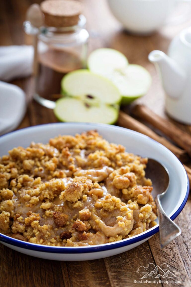 Apple crumble in a bowl with slices and cinnamon sticks